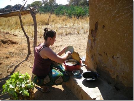 Washing dishes outside hut